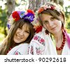 Two girls in national slavic costumes at outdoor. - stock photo