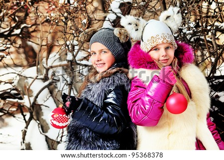 Two girls in Santa Claus cap celebrating Christmas at a winter park.