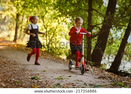 Two  girls in school uniform playing in the park and riding on scooter - stock photo