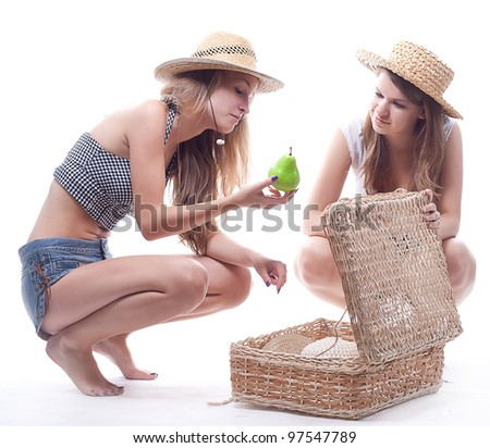 Two girls in straw hats  suitcase near the studio photography - stock photo