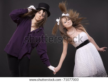 Two girls in suits keep for hands