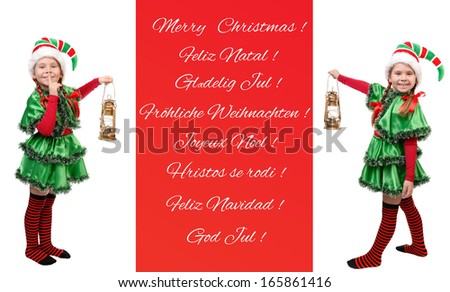 Two girls in suits of the elf with small lamps and a banner with Christmas inscriptions in different languages - stock photo