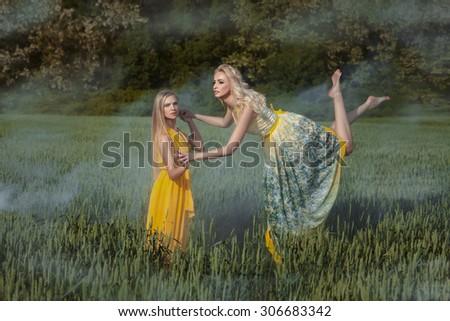 Two girls in the field. One girl levitates. Around haze. - stock photo