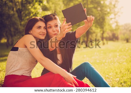 Two girls in the park taking selfie with tablet - stock photo