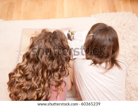 Two girls is reading magazine. Rear view - stock photo