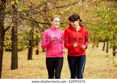 Two girls jogging in autumn park and smiling - stock photo
