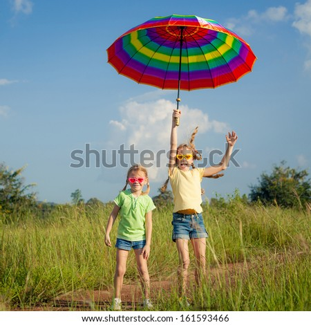 Two girls jumping on the road with an umbrella - stock photo