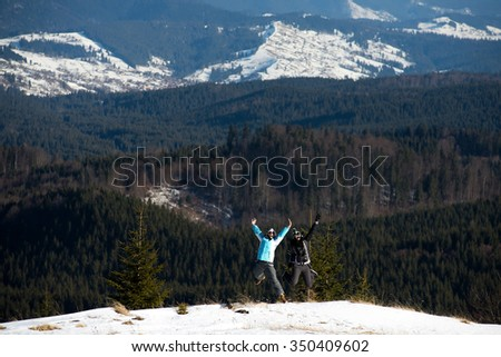Two girls jumping together in wintertime. Mountain background. - stock photo