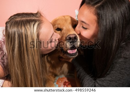 Two girls kissing a golden retriever dog