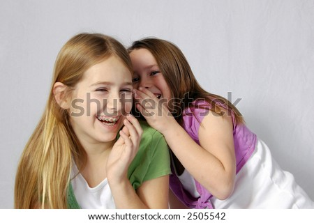 Two girls laughing at a shared joke - stock photo