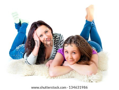 Two girls lie comfortably on the floor