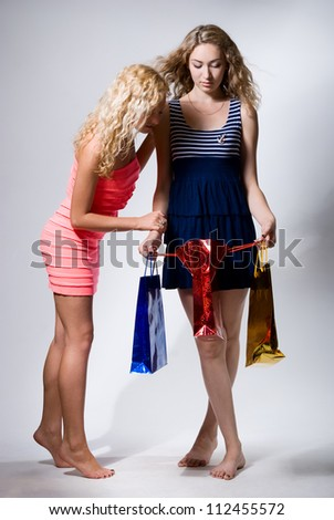 Two girls look in a red paper package for purchases. Shop visit
