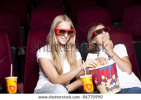 two girls look three-dimensional cinema, sitting in the glasses, eat popcorn, drink drink - stock photo