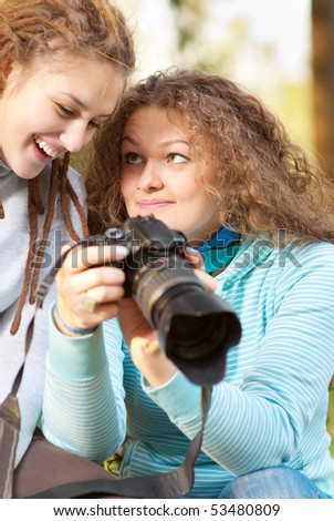 Two girls look through pictures on SLR-camera