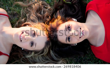 Two girls lying in the countryside with a nice reflection of the sun - stock photo