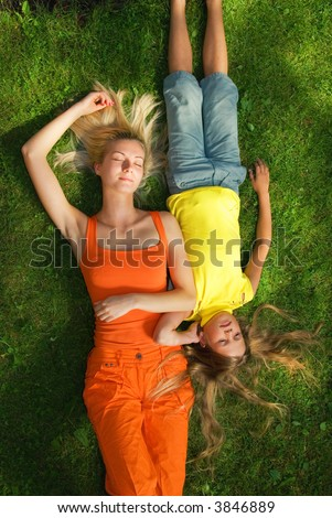 Two girls lying on a green grass - stock photo