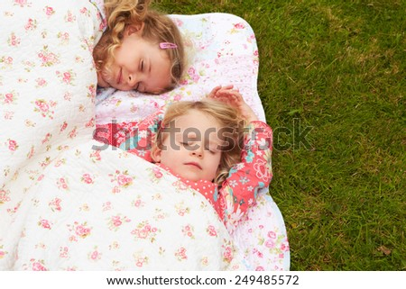Two Girls Lying Under Blanket On Camping Holiday  - stock photo