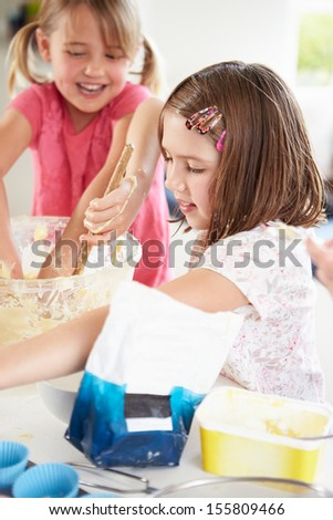 Two Girls Making Cupcakes In Kitchen