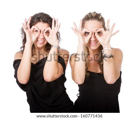 two girls mime glasses with hands - stock photo