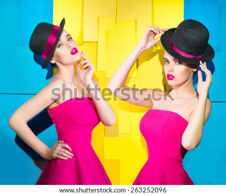Two girls on a bright background in hats  - stock photo