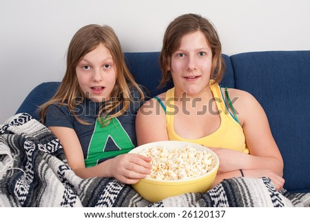 two girls on sofa eating popcorn and watching tv - stock photo