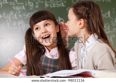 two girls on the background of the school board - stock photo