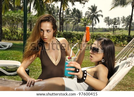 Two girls on the beach put the sunblock cream on each other - stock photo