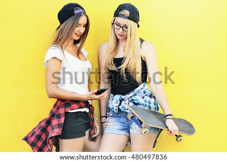 Two girls  on the playground watching the news in the smartphone in social networks. Young women in shirts, shorts and baseball caps on yellow background.