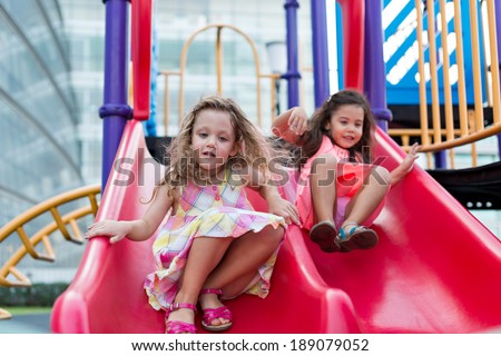 Two girls on the red slide - stock photo