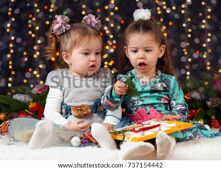 two girls open gift boxes in christmas decoration, dark background with illumination and boke lights, winter holiday concept