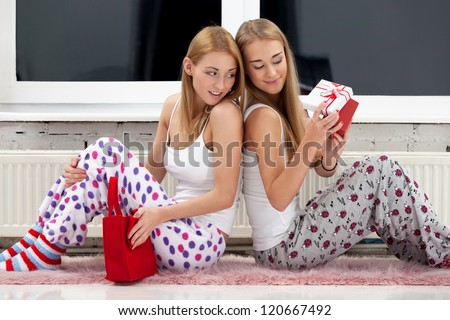 Two girls opening christmas gifts - stock photo