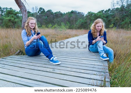 Two girls operating mobile phones sitting on wooden path in nature - stock photo