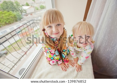 Two girls play at the windows-sill in pyjamas before sleep  - stock photo