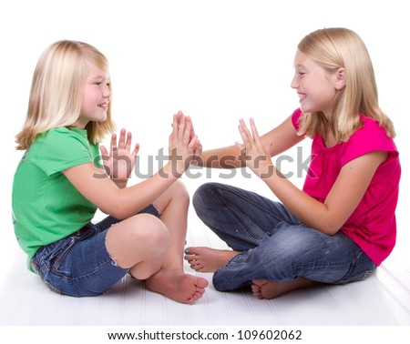 two girls playing clapping game, white background - stock photo