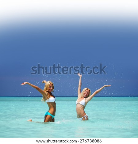 Two girls playing in ocean water - stock photo