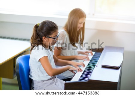 Two girls playing the piano at the music school, selective focus