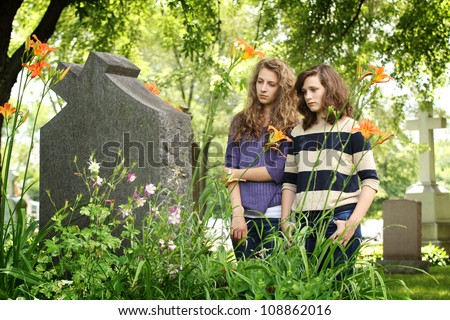 Two girls praying in front of a tomb in a cemetery