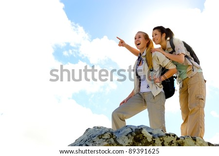 two girls reach the summit of a climb and point out at the view - stock photo