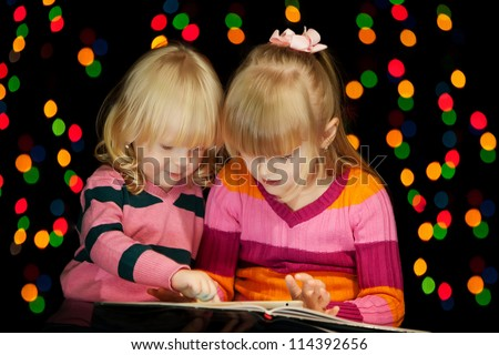 Two girls read book of tales on the Cristmas Eve - stock photo