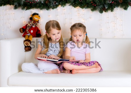 two girls reading a book in the Christmas decorations - stock photo