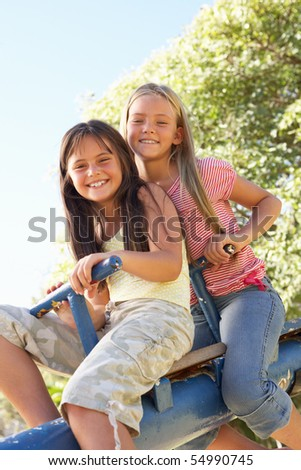 Two Girls Riding On See Saw In Playground - stock photo