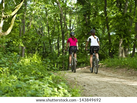 two girls riding the bicycle in the forest - stock photo