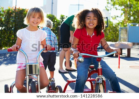 Two Girls Riding Tricycles In Playground