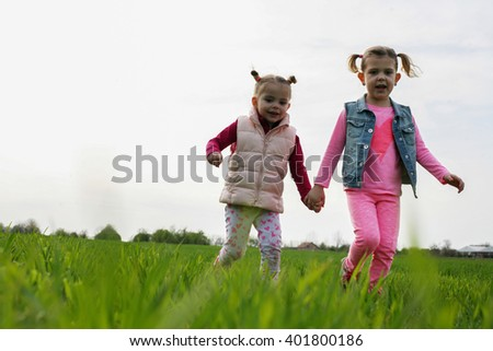 Two girls running and having fun on a meadow. - stock photo
