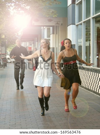 two girls running away from an angry boyfriend or business owner - stock photo