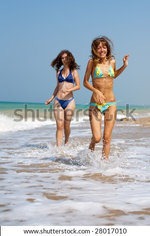 Two girls running on seashore