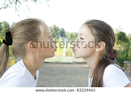 Two girls send air kisses