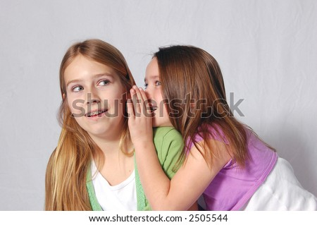 Two girls sharing a secret - stock photo