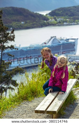 two girls sisters sitting on a bench in the town of Alesund and the mountains to the fjord in the background, norway