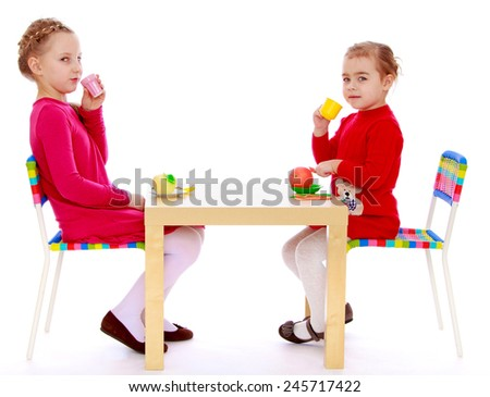 Two girls sitting at the table and drink tea.Isolated on white background - stock photo